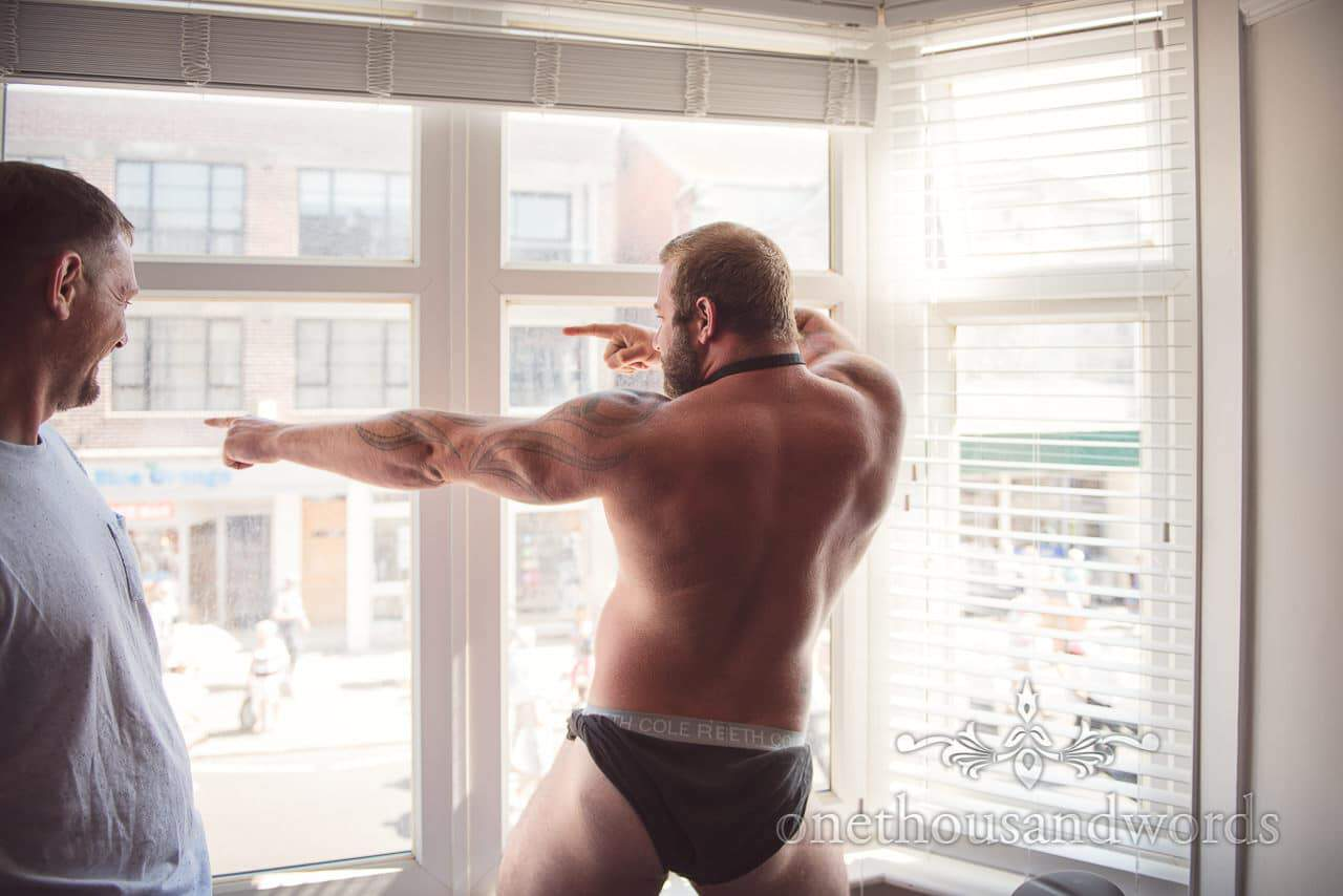 Dancing groomsman in window before Purbeck courtyard Wedding