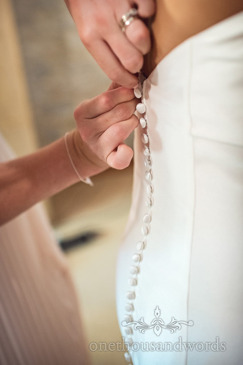 Detail wedding photograph of bride being buttoned into her white wedding dress