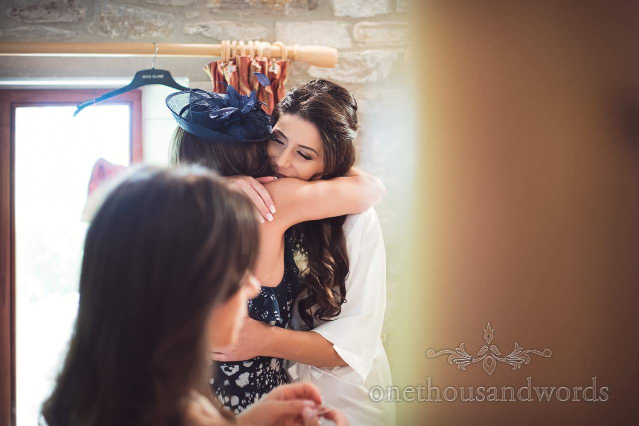 Documentary photo of bride and mother of the bride hugging on wedding morning