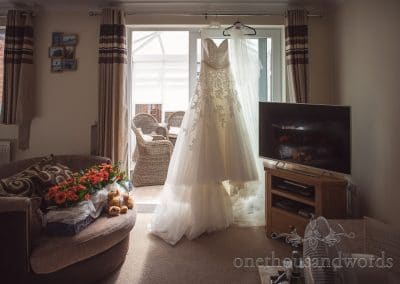 Dress hangs and is lit up by sunlight from RNLI College Wedding Photographs