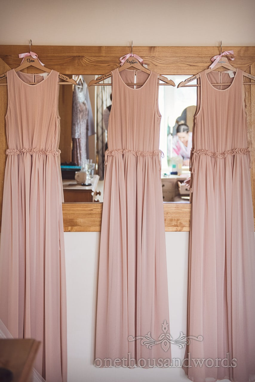 Dusty pink bridesmaids dresses with personalised hangers on wooden framed mirror