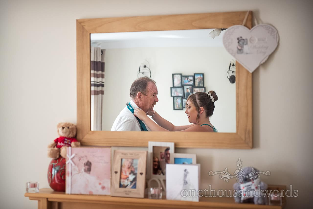 Father of the bride has help with his cravat on wedding morning