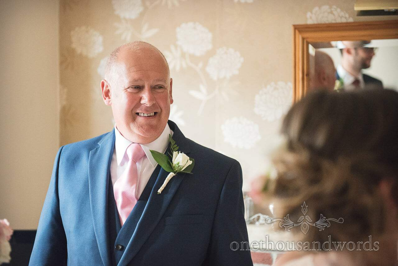 Father of the groom in blue suit and pink tie looks at bride on wedding morning