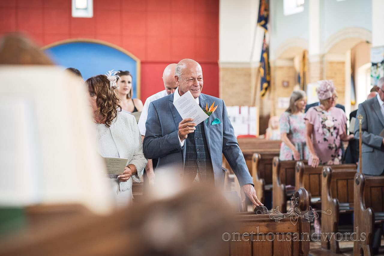 Father of the groom smiles during church wedding ceremony in Poole, Dorset