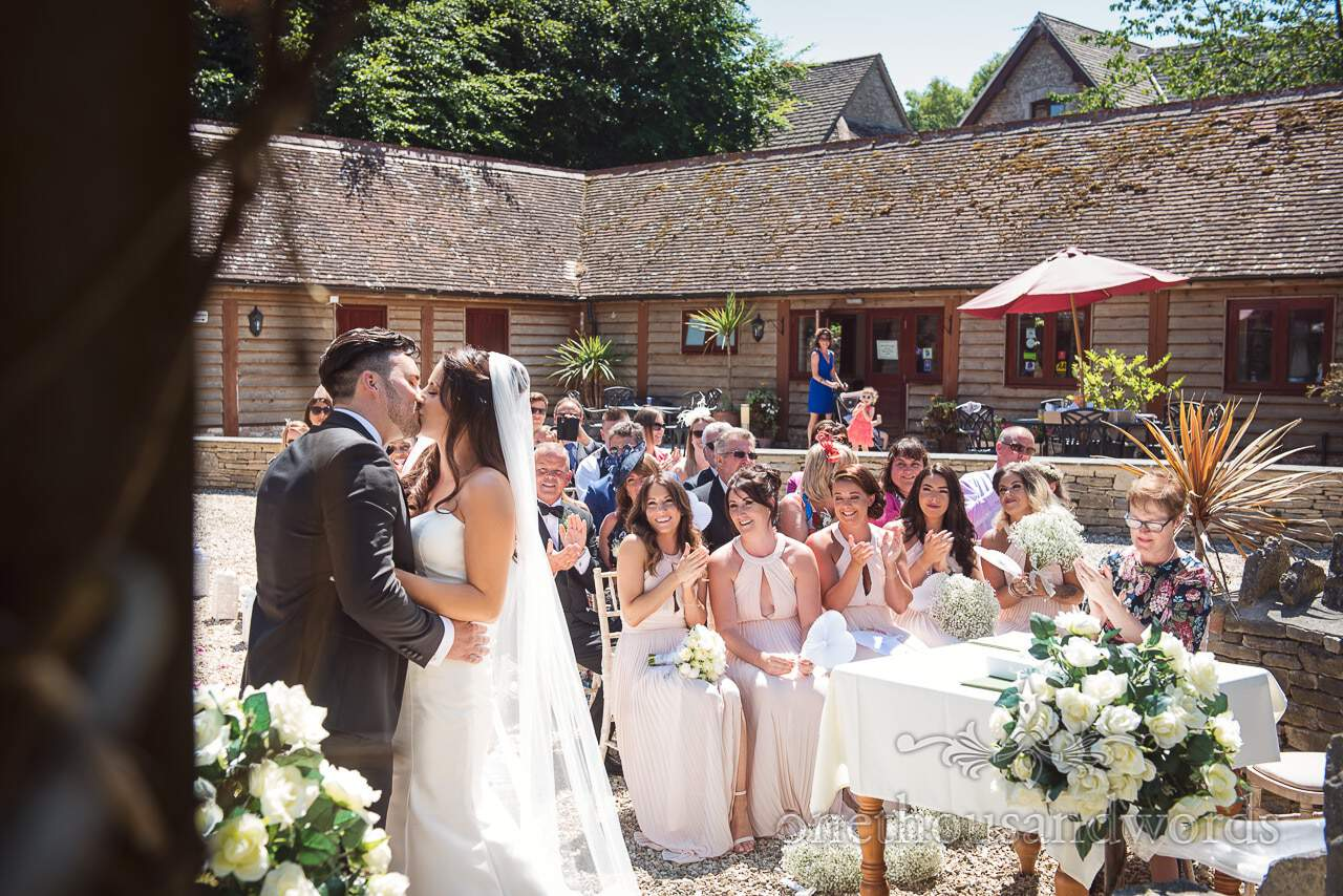 First kiss at outdoor Country Courtyard Wedding