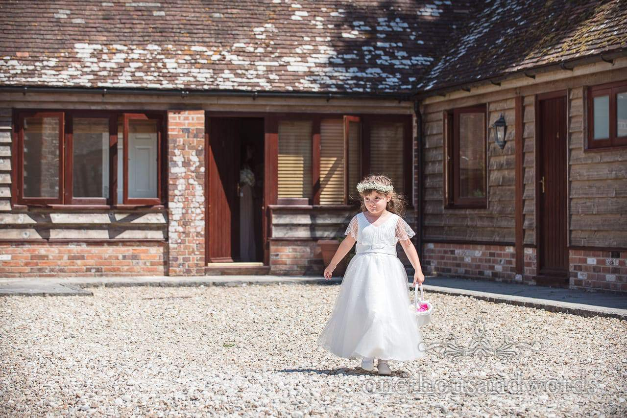 Flower girl leads bridal party out in the sunshine at Country Courtyard Wedding