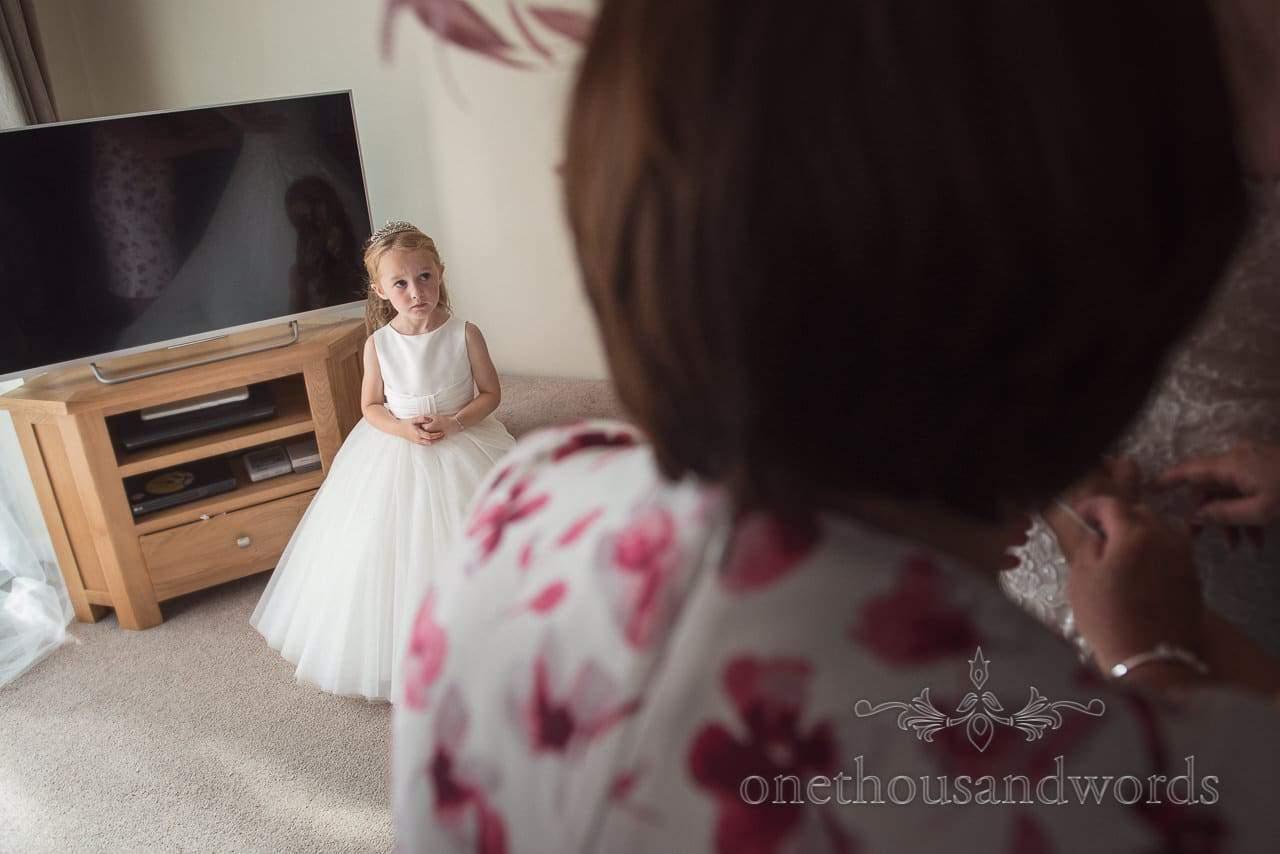 Flower girl watches bride putting on her wedding dress on wedding morning