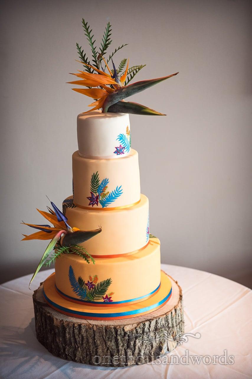 Four tier orange graded wedding cake with bird of paradise flowers