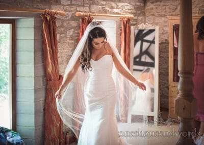 Gorgeous bride in white wedding dress fans out wedding veil during bridal preparation
