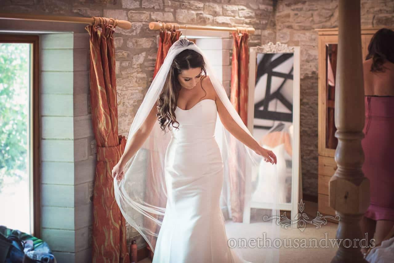 Gorgeous bride in white wedding dress fans out wedding veil during bridal preparation