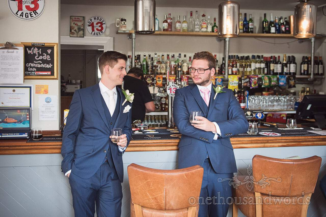 Groom and best man in blue suits prop up pub bar on wedding morning in Swanage