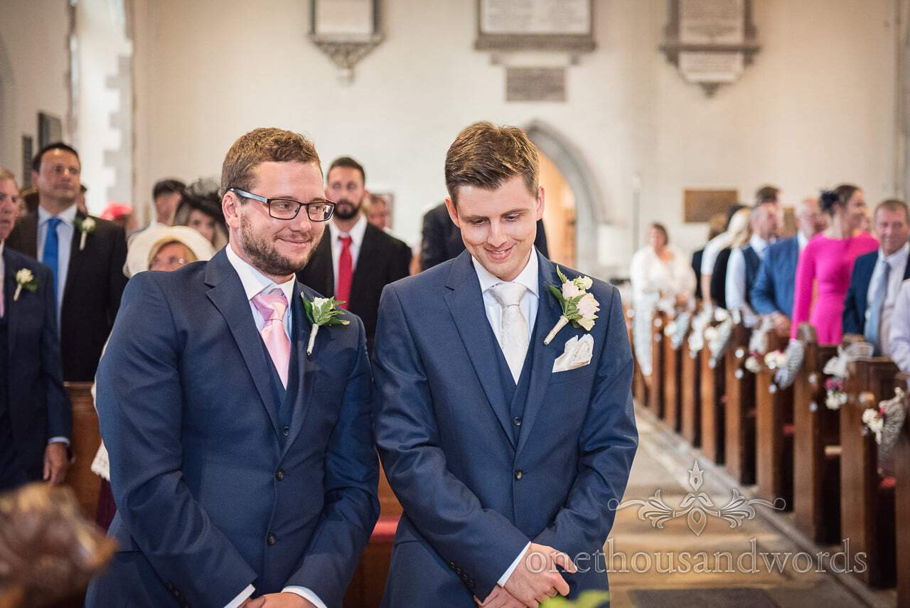 Groom and best man smiling as they wait for the entrance of bride in church