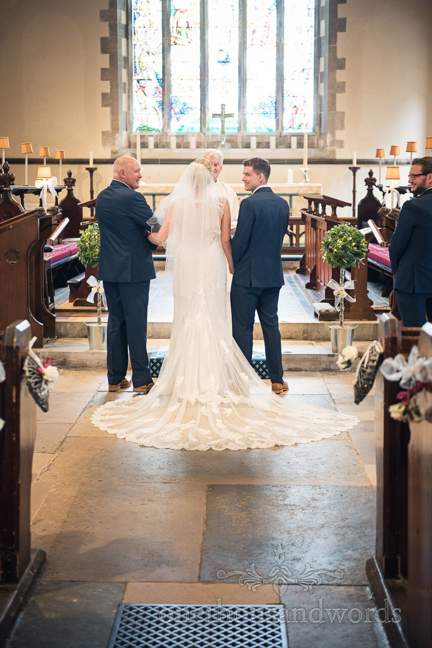 Groom and bride's father look around from alter at church wedding ceremony