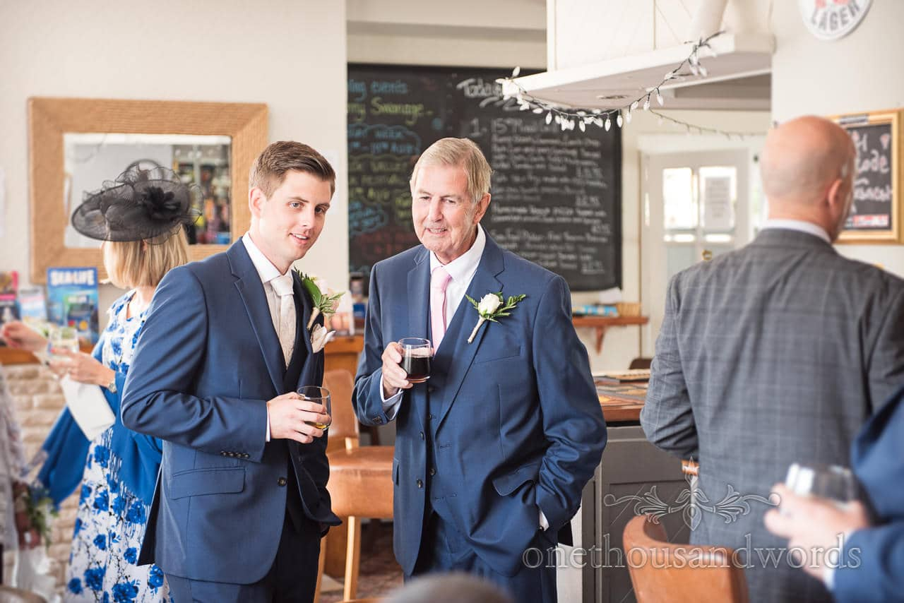 Groom and father of the groom share a drink in pub on wedding morning in Dorset