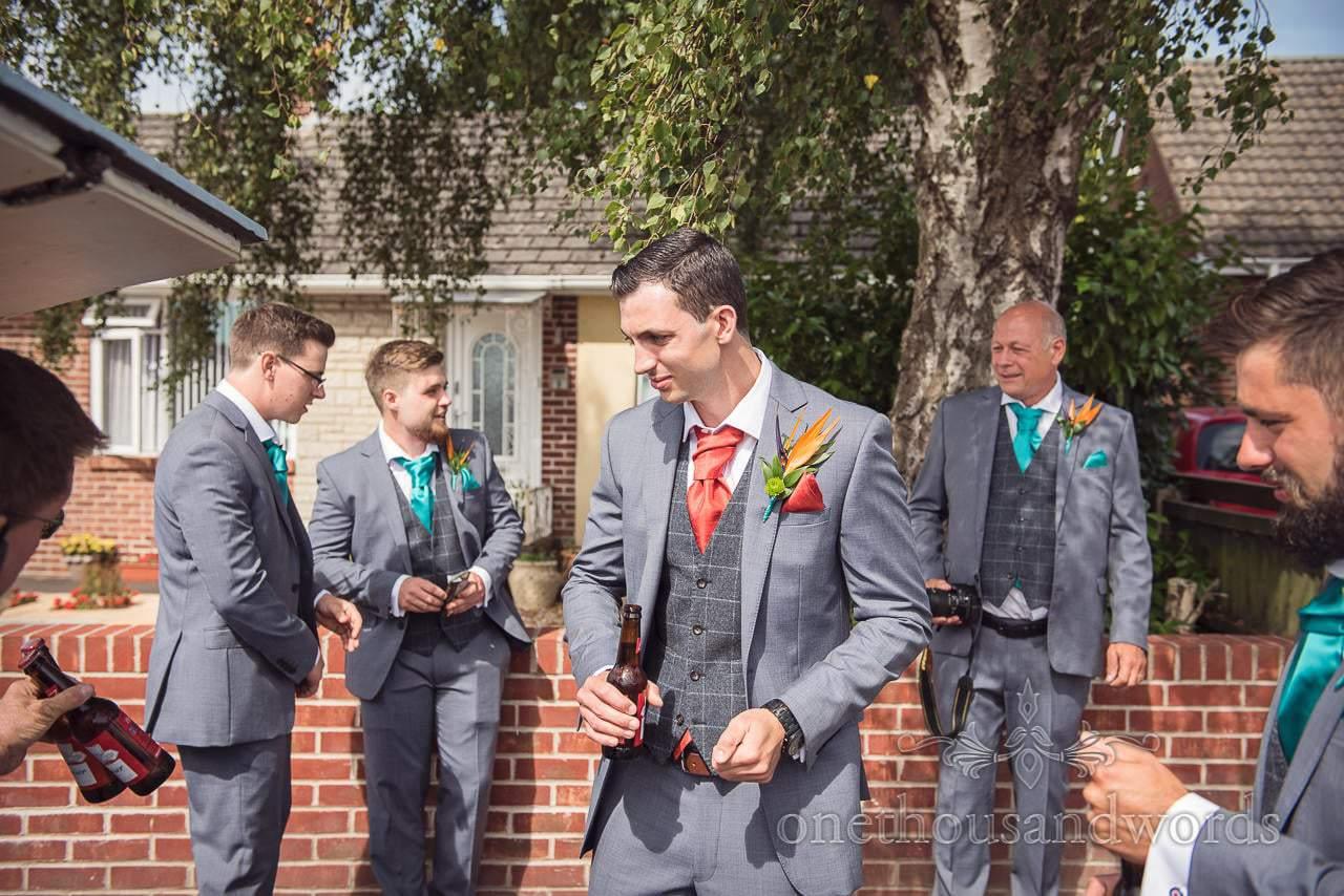 Groom and grooms men in grey suits enjoy a wedding morning beer