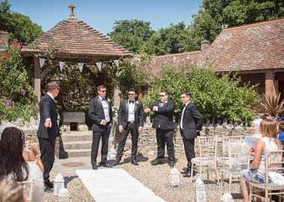 Groom and groomsmen in black suits await bride at Country Courtyard Wedding