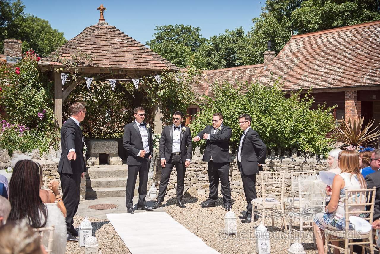 Groom and groomsmen in black suits await bride at Country Courtyard Wedding