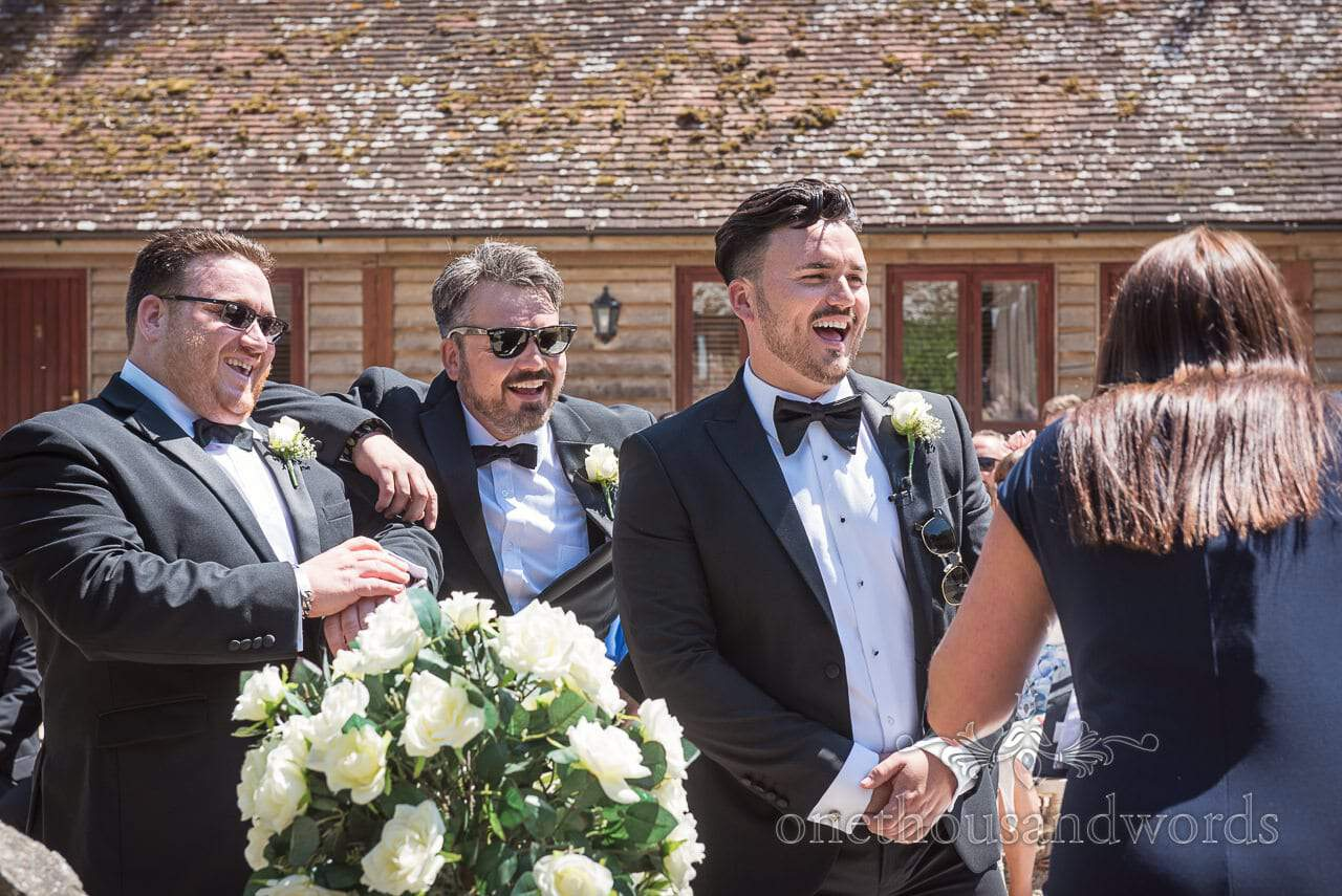 Groom and groomsmen share a joke from Country Courtyard Wedding