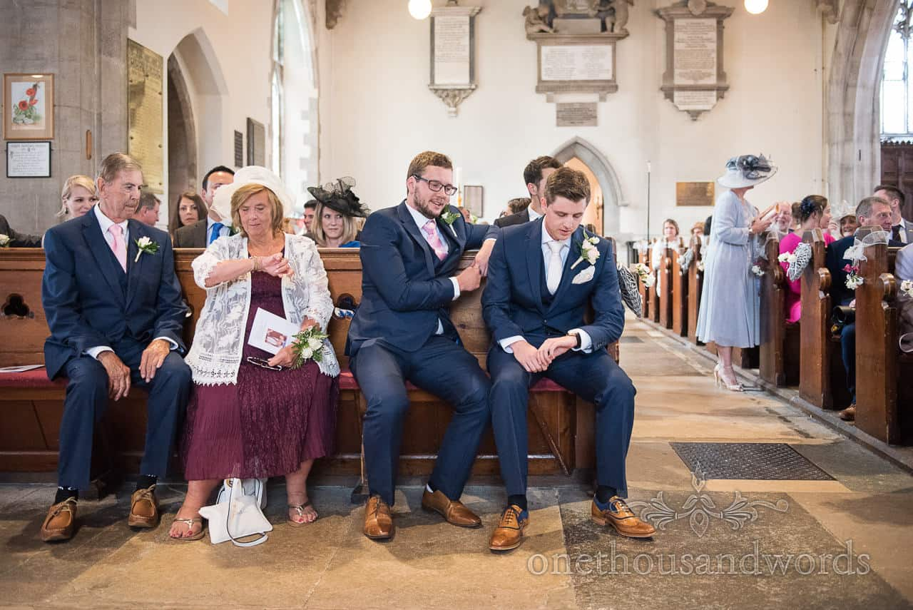 Groom and parents check the time waiting for bride in church wedding ceremony
