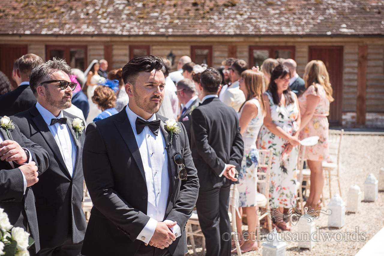 Groom awaits his bride in the sunshine at Country Courtyard Wedding