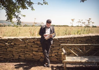 Groom in black suit reads letter from bride against countryside stone wall