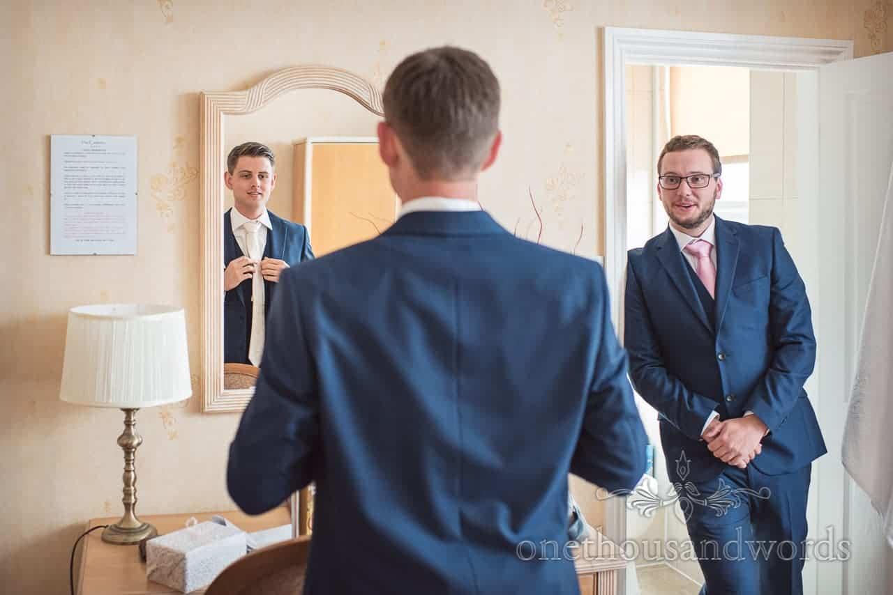 Groom in blue suit ties pink wedding tie in mirror watched by best man