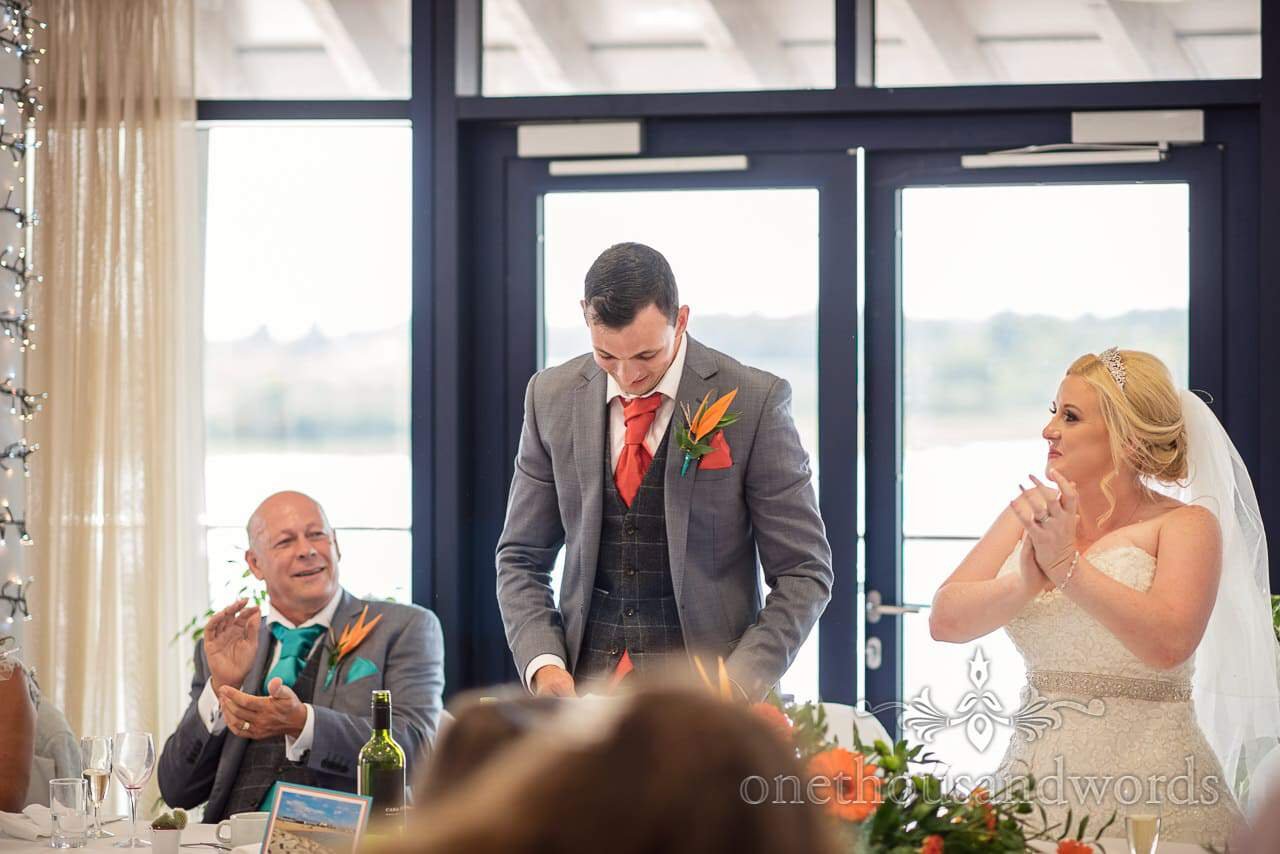 Groom in cheque tweed and grey delivers wedding speech at RNLI College Wedding