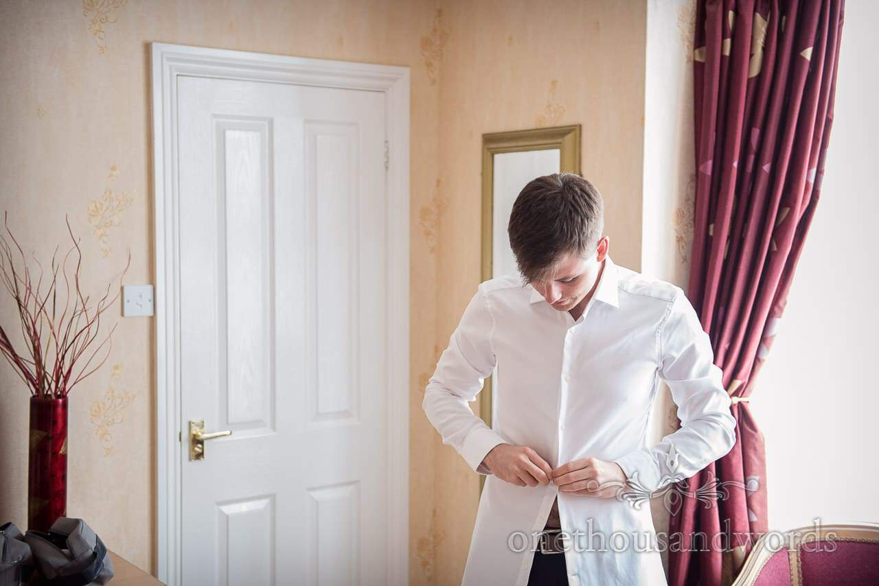 Groom puts on white shirt during wedding morning groom preparations