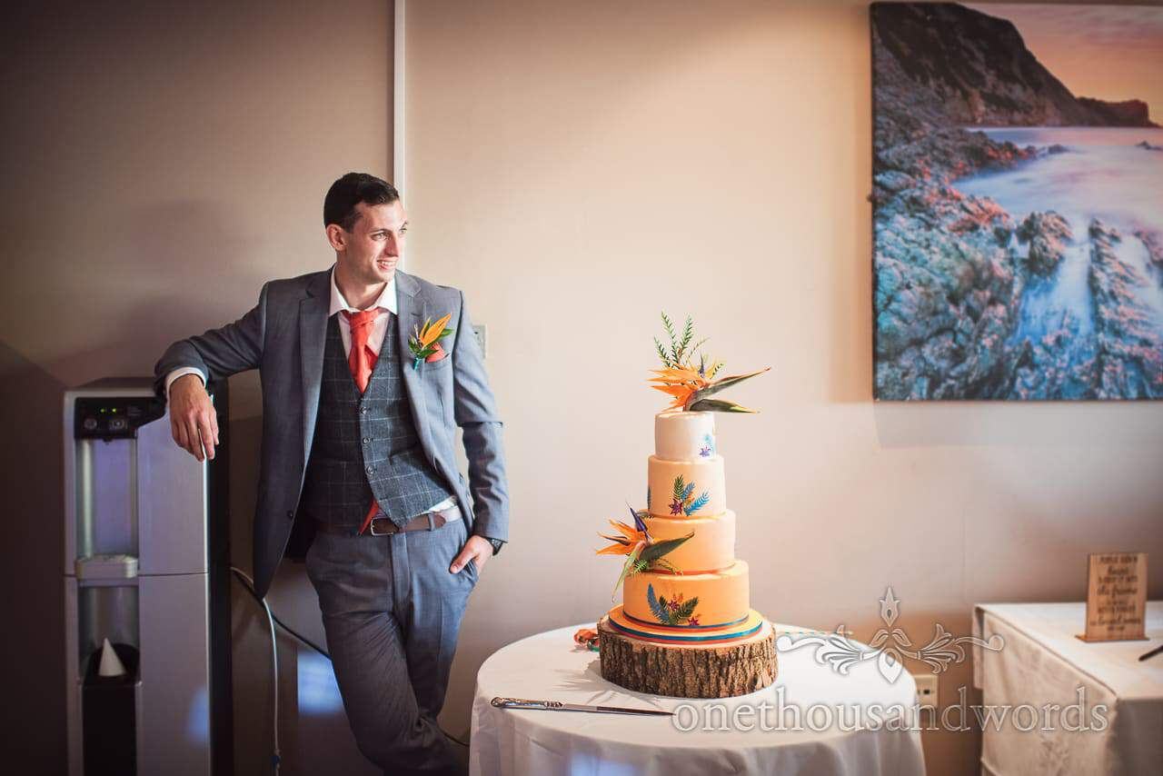 Groom waits next to wedding cake at RLNI College Wedding venue in Poole