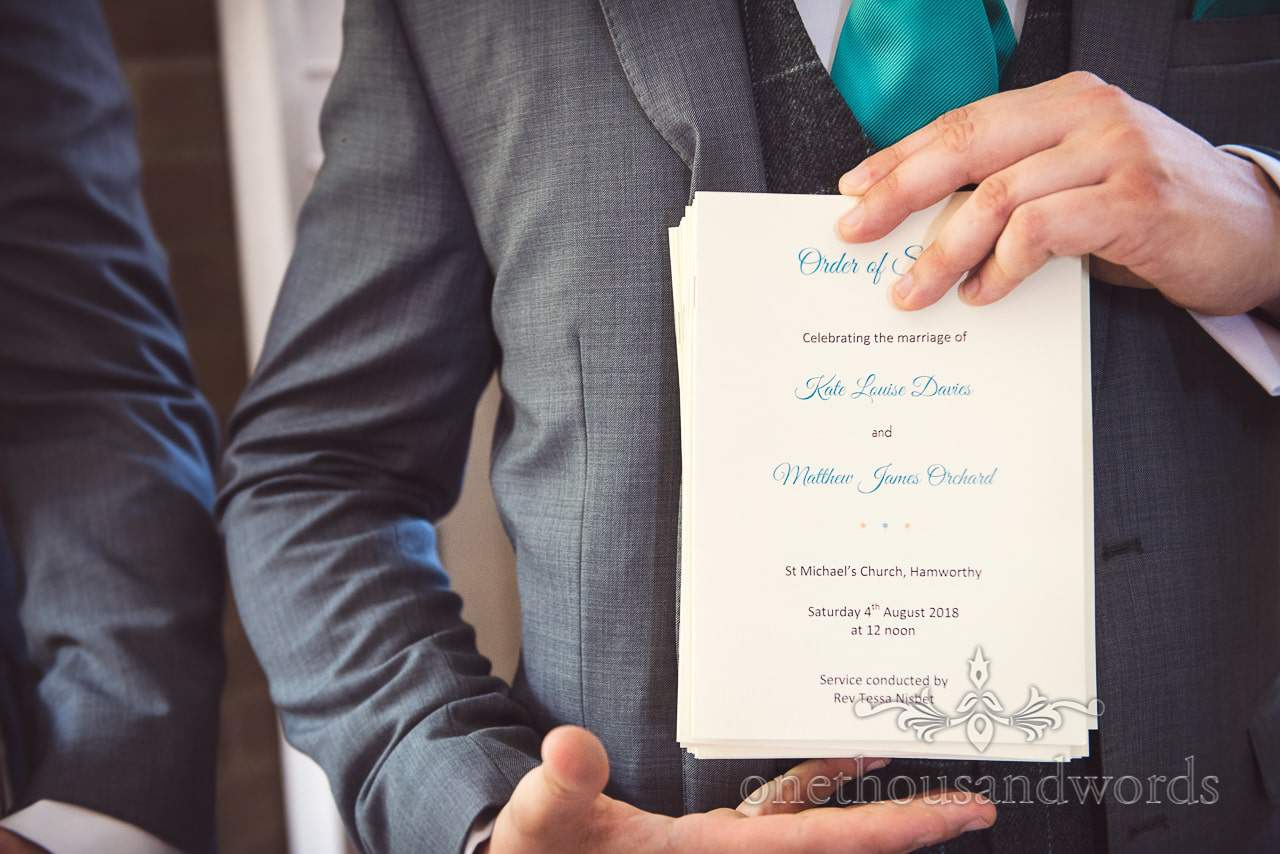 groomsmen hold church order of service for wedding ceremony in Dorset