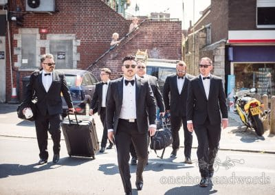 Groomsmen in black suits and bow ties walk across the street like reservoir dogs