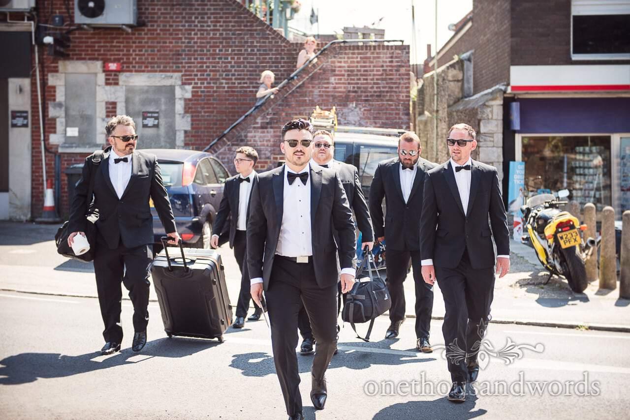 Groomsmen in black suits and bow ties walk across the street like reservoir dogs