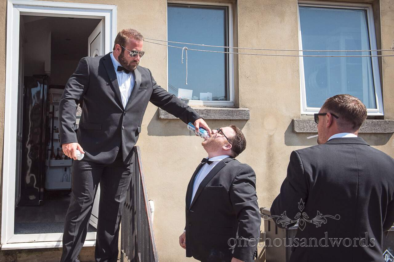 Groomsmen in black suits spray cream into each others mouths on wedding morning