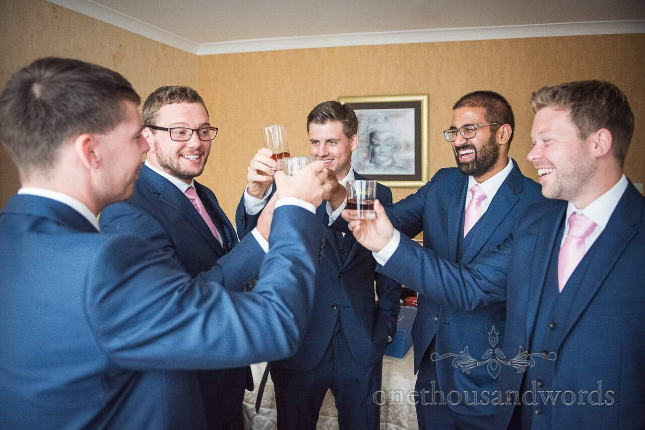 Groomsmen in blue three piece suits toast with spirits on wedding morning