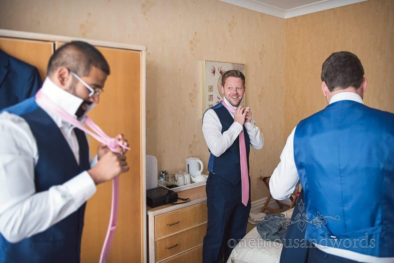 Groomsmen in blue waistcoats tie pink wedding ties during groom preparation