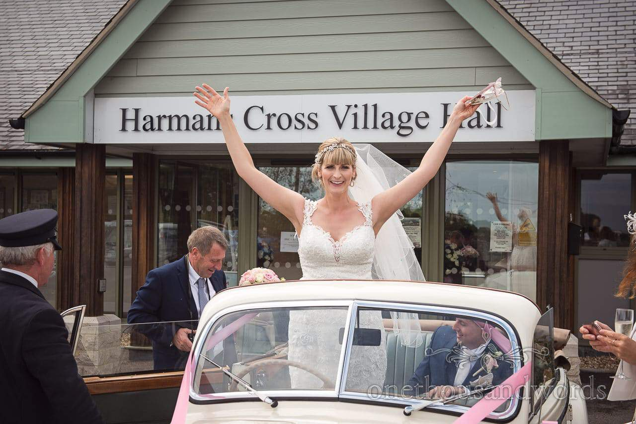 Harmans Cross Village Hall Wedding Photographs of bride in open top wedding car