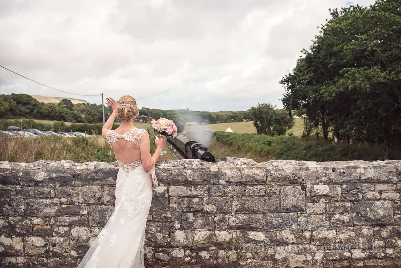 Harmans Cross Village Hall Wedding Photographs of bride waving at steam train
