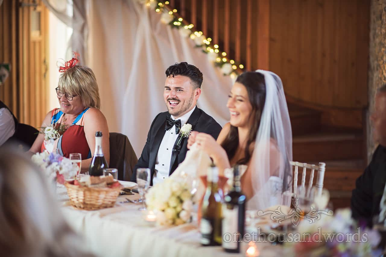 Laughing groom at top table during speeches at Country Courtyard Wedding
