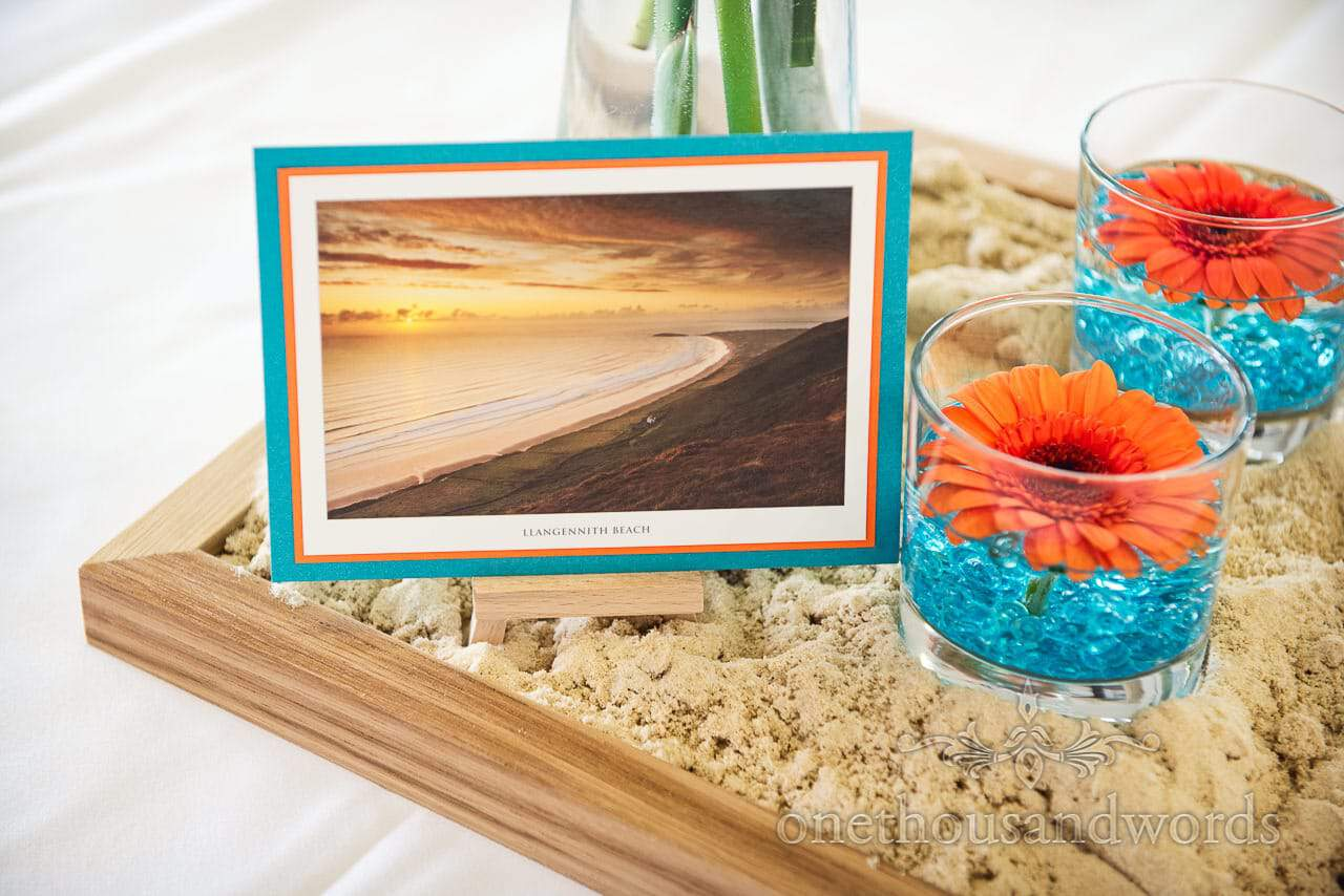 Llangennith Beach postcard wedding table name decoration in sand tray with flowers