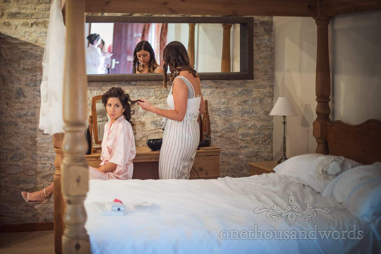 Maid of honor has hair styled before courtyard wedding