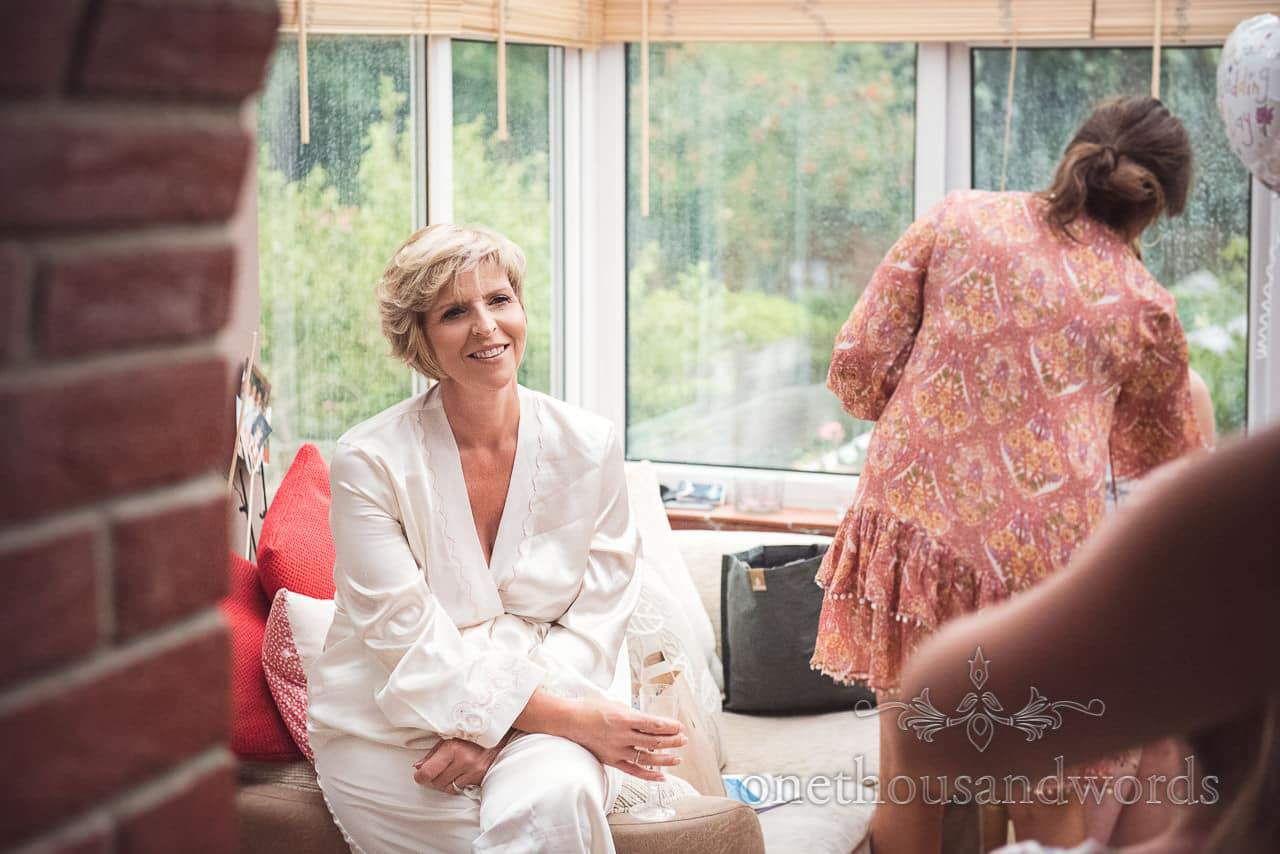 Mother of bride in silk dressing gown watches bridal preparation on wedding morning