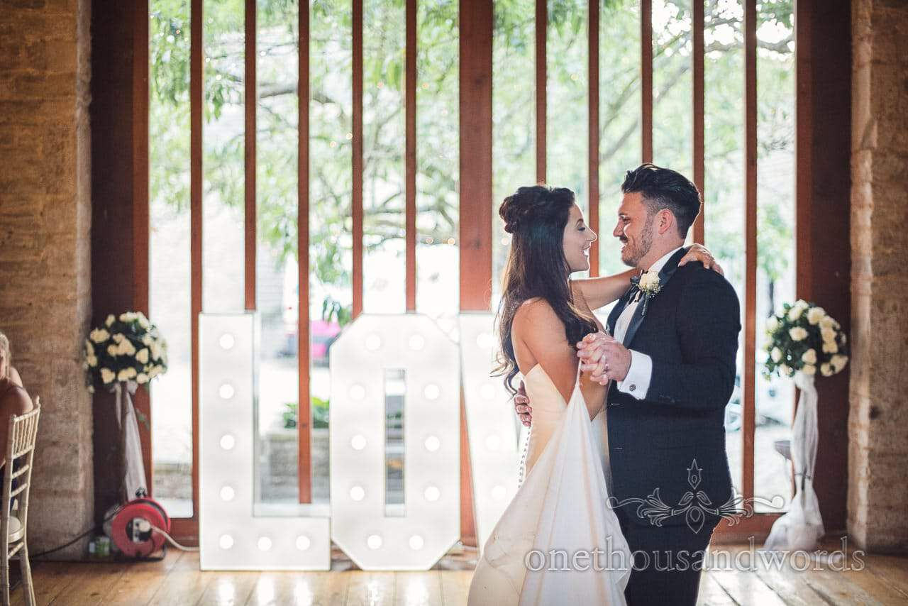 New Mr and Mrs dance in front of love letters at Purbeck Courtyard Wedding
