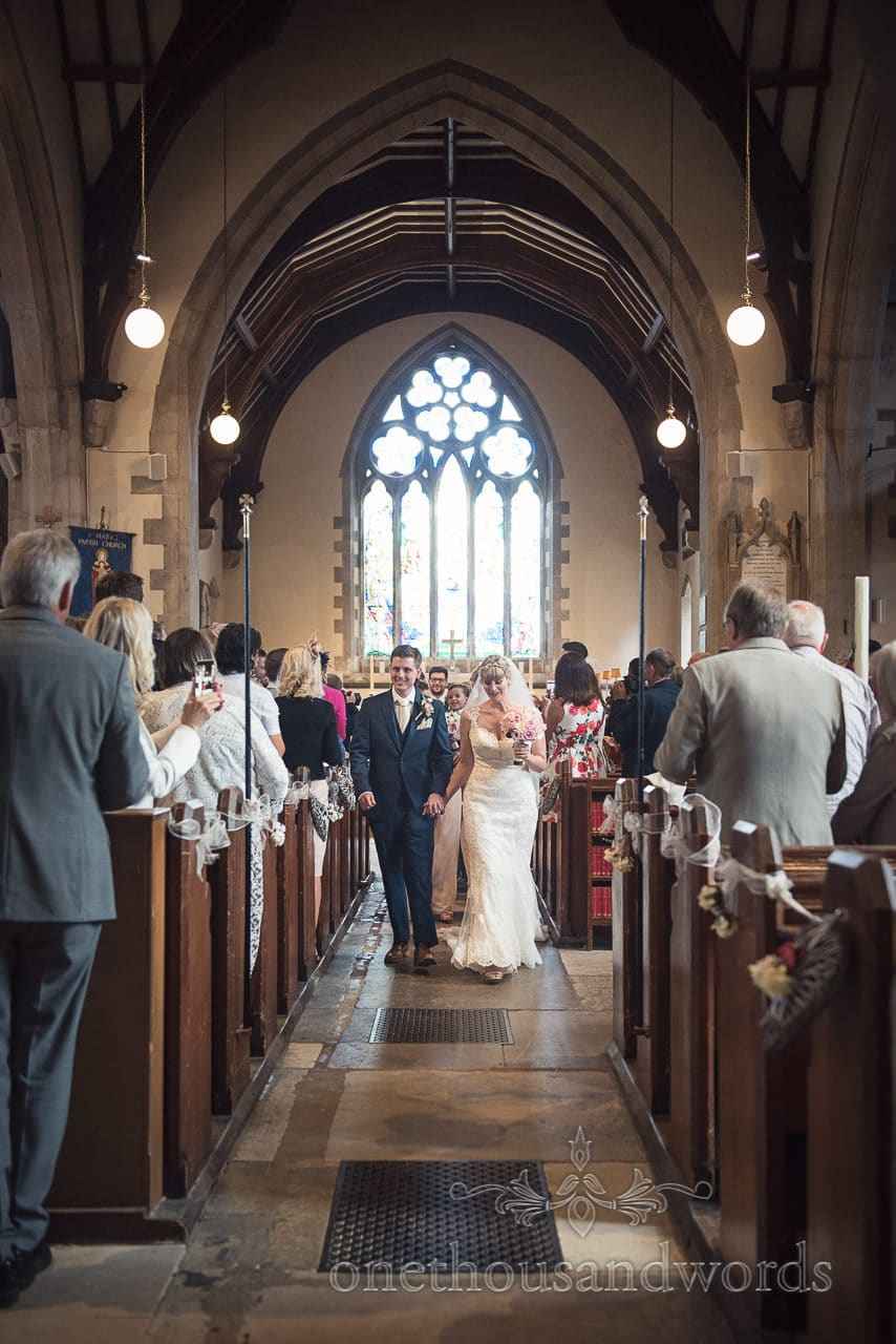 Newly wed bride and groom walk down church aisle after wedding ceremony