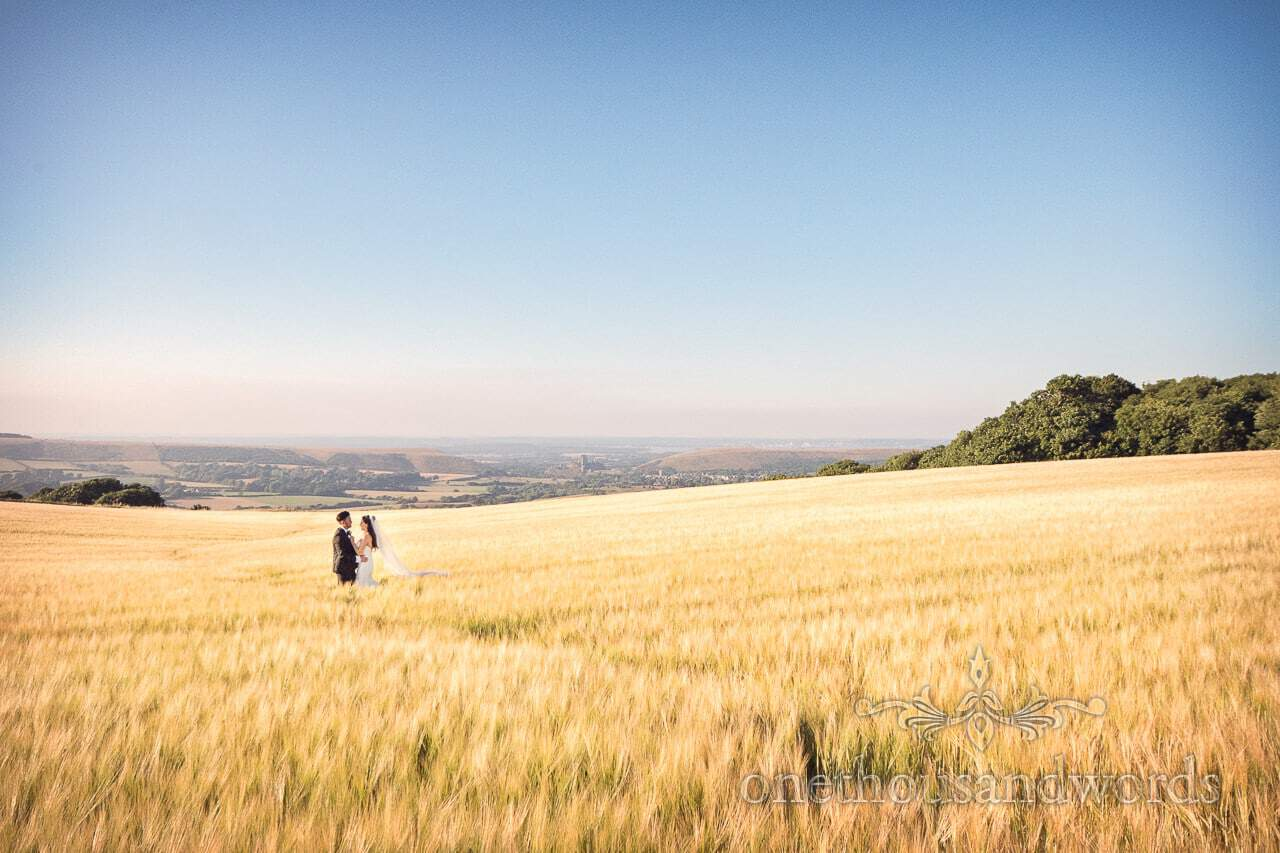 Newlyweds in field overlooking Purbeck countryside from Courtyard Wedding