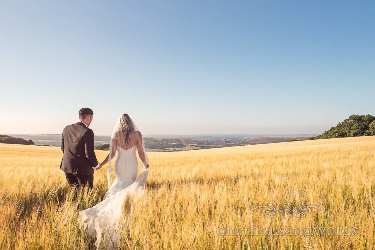 Newlyweds walk across field from Country Courtyard Wedding