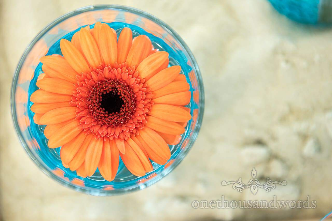 Orange Gerbera in glass of blue beads wedding table decorations