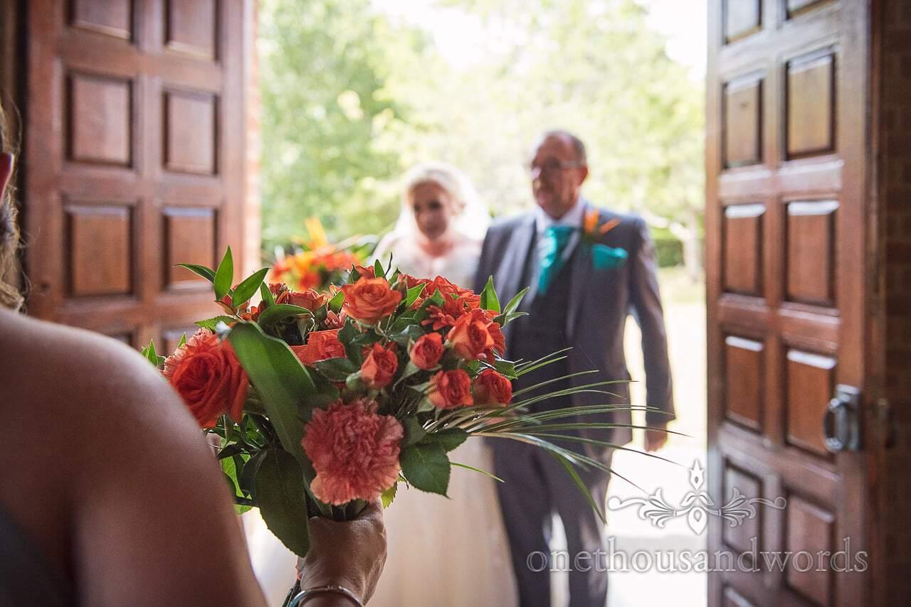 Orange wedding flower bouquet with bride and her father at church doorway