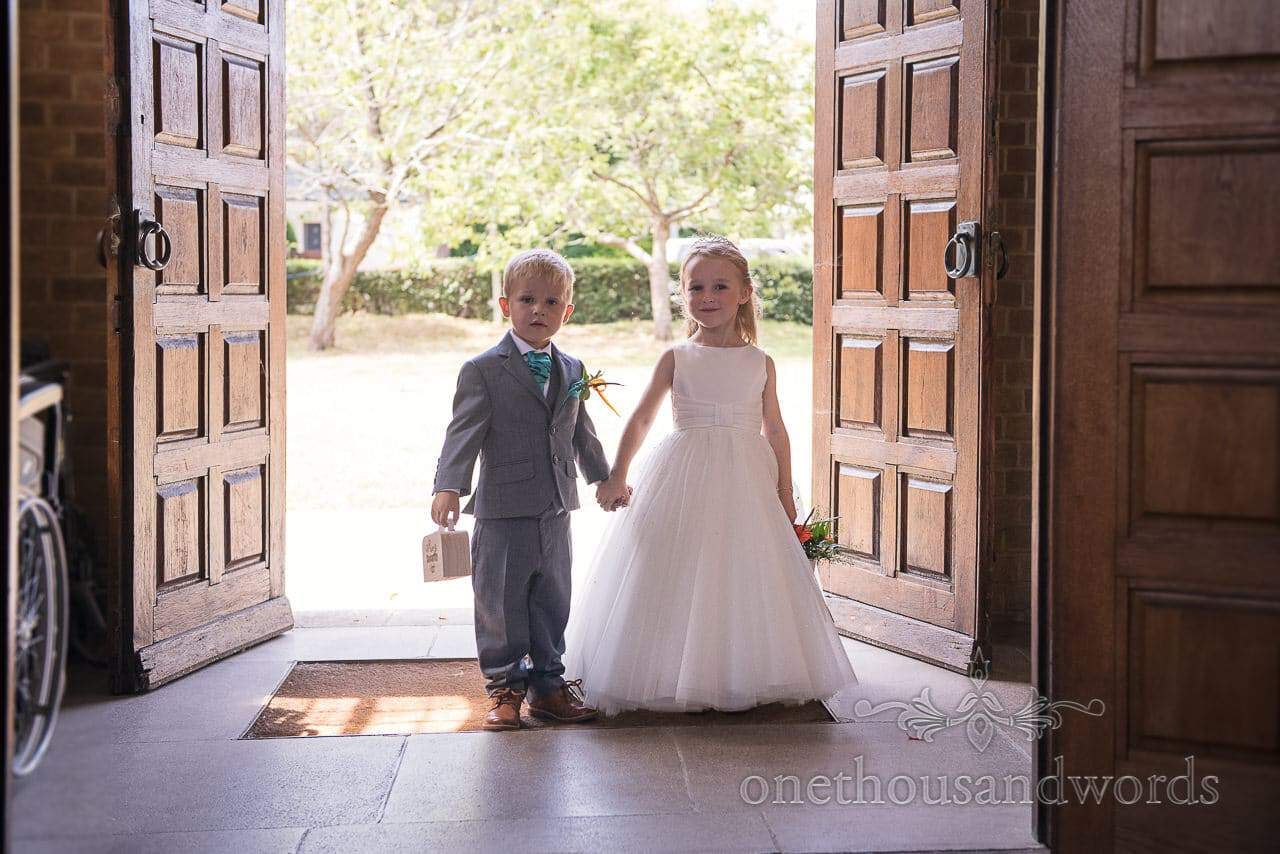 Page boy and flower girl wait in church doorway at wedding ceremony in Poole