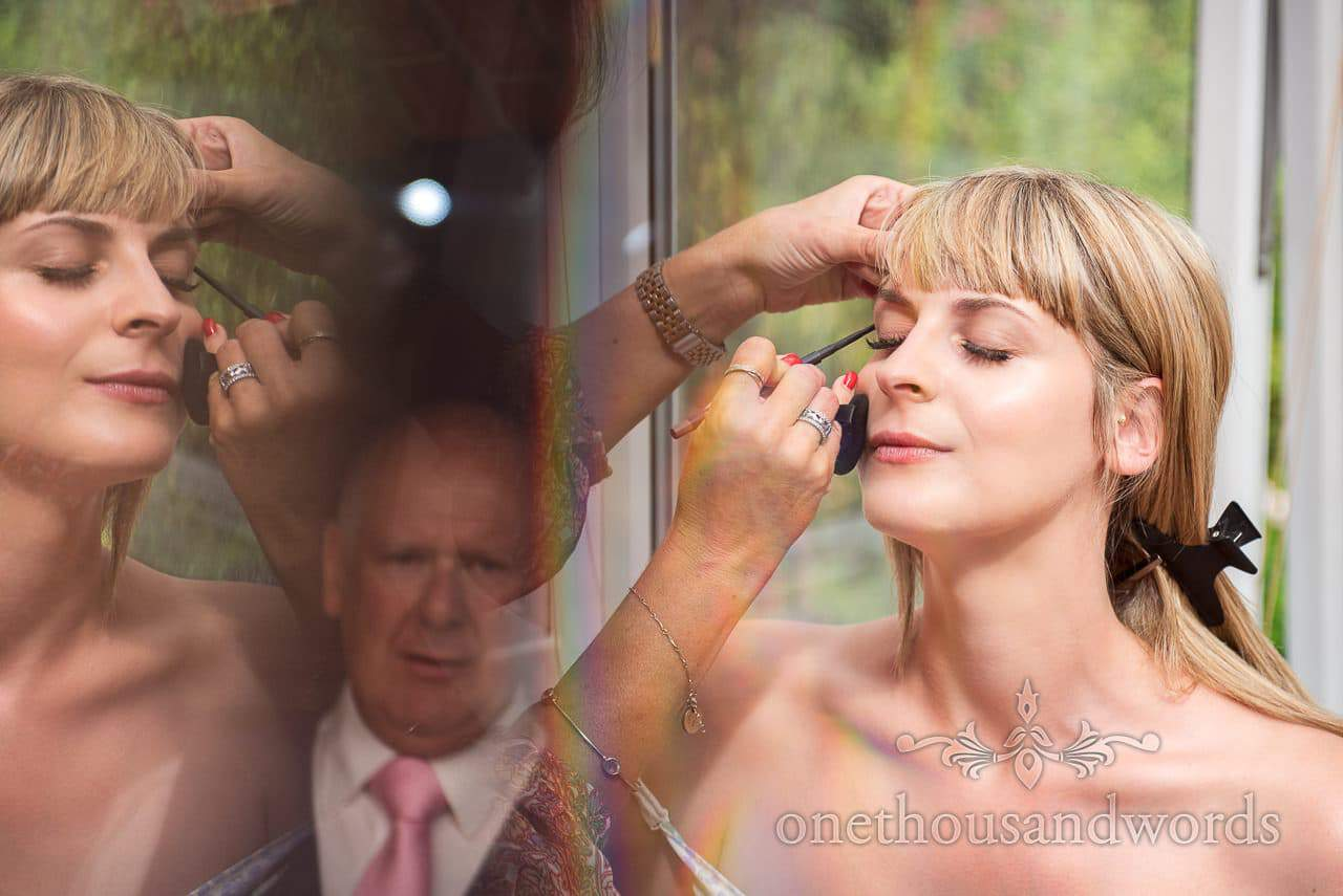 Reflection of father watching bride have wedding make up applied during bridal prep
