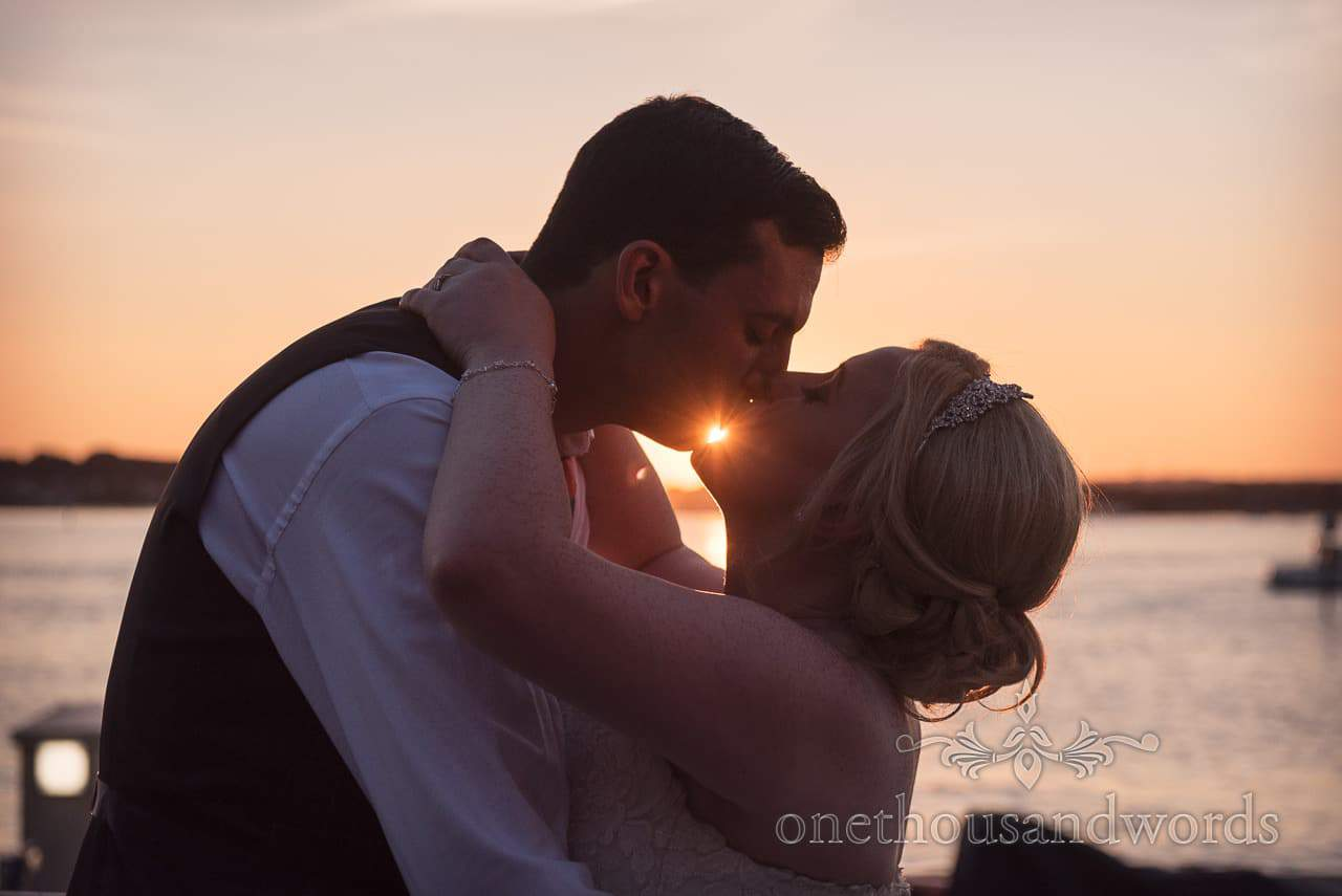 RNLI College wedding photographs Bride and groom kissing at sunset